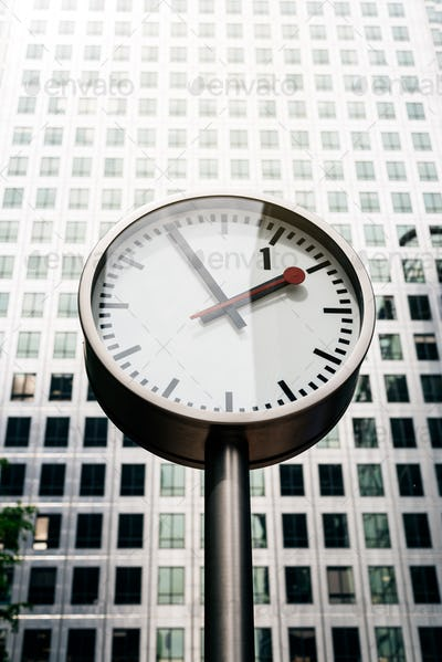 Street clock with tall building on the background