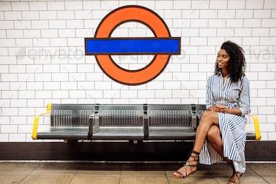 Black woman using mobile phone at london underground