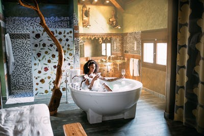 Woman relaxing in the hydro massage bath covered in foam with mobile phone