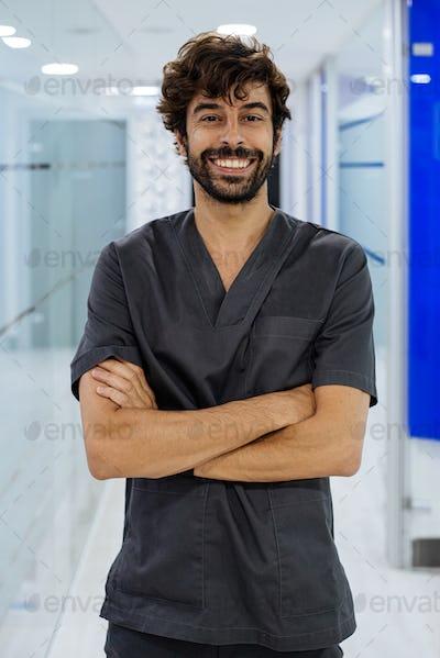 elegant confident man doctor dentist wearing lab coat looking at camera