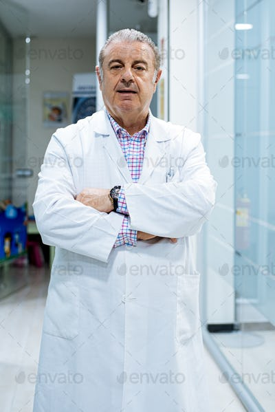 elegant aged confident man doctor dentist wearing lab coat looking at camera