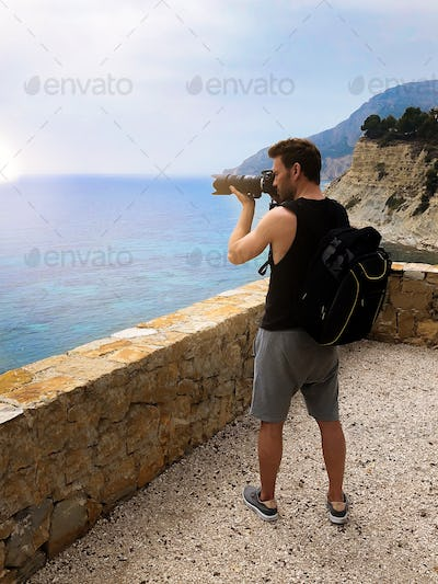 Photographer taking a picture of a ocean coast