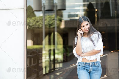 Young beautiful woman happy with her phone talking and texting a message
