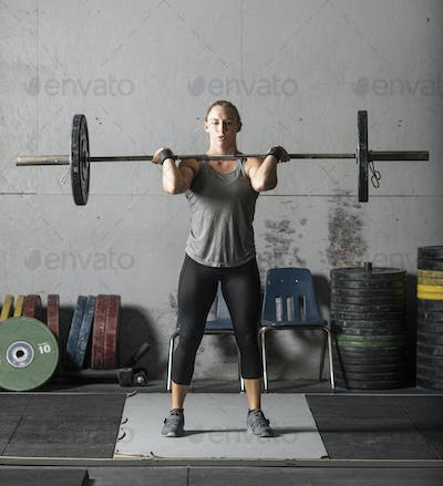 Young beautiful female power lifter lifting barbell in grungy gym.