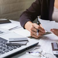 Stressed young woman checking bills, tax and calculating expenses at home