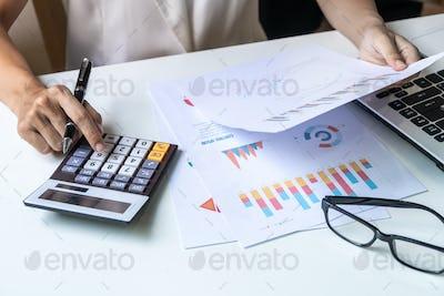 Businesswoman working on Desk office with marketing graph statistics analysis