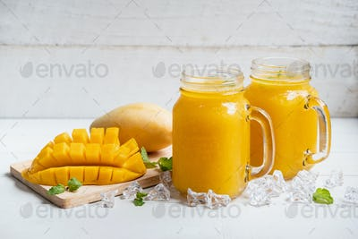 Refreshing mango smoothies in glass with ripe mango on white wooden table