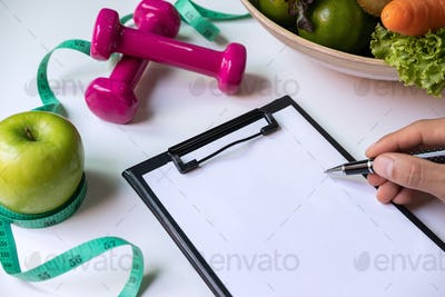 Clipboard with healthy fruit, vegetable and measuring tape on nutritionist desk