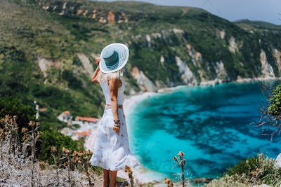 Young woman on Petani beach Kefalonia, admiring highly excited picturesque panorama of emerald blue