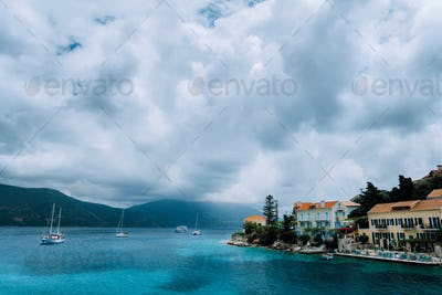 Cloudscape over Fiskardo village buildings with orange brick roofs. Yacht boats looking for shelter