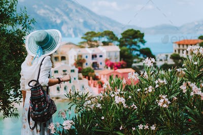 Elegant woman with straw hat and white clothes enjoying view of colorful village Assos on sunny day