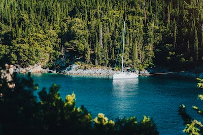 White sail boat yacht moored in the bay of Foki beach with cypress trees in background, Fiskardo