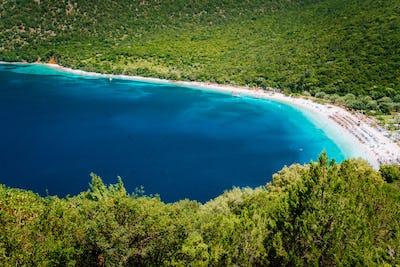 Sunny summer day on Antisamos beach on Kefalonia island, Greece. Crystal clear water, huge hills