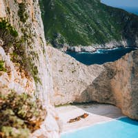 Navagio beach. Pure turquoise azure cyan teal blue sea water surrounded by huge white limestone