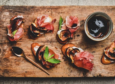 Crostini with prosciutto, cheese and figs on wooden board