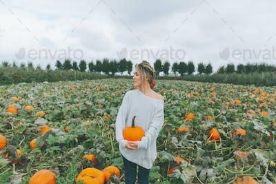 A Woman Holding a Pumpkin in a Pumpkin Patch