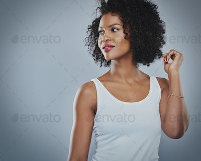 Smiling flirting woman in white top, grey background
