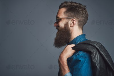 Stylish man wearing sunglasses carrying a jacket over his shoulder