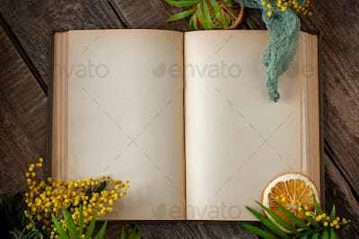 An open old book with blank pages and floral decor on an old woo