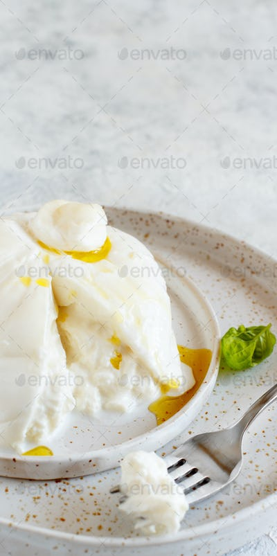 Italian cheese burrata on a plate with a fork and basil