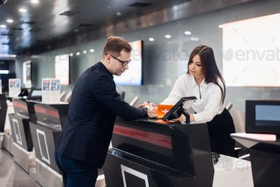 Business trip. Handsome young businessman in suit holding his passport and talking to woman at