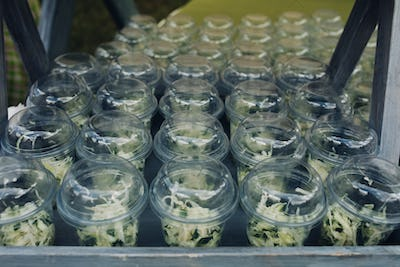 Organic veggies in cups to go.Close-up of loads of plastic cups filled with chopped vegetables and