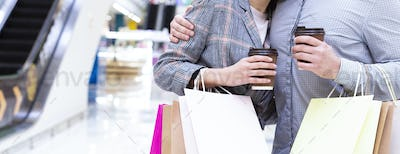 Loving couple shopping in mall with coffee, holding paper bags