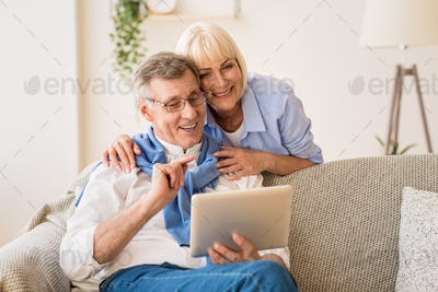 Happy pensioners using tablet, relaxing on rug