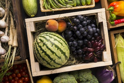Eco fruits watermelon and grapes in wooden box outdoor