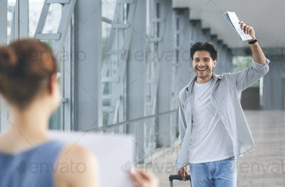 Passenger walking with luggage to woman with name board