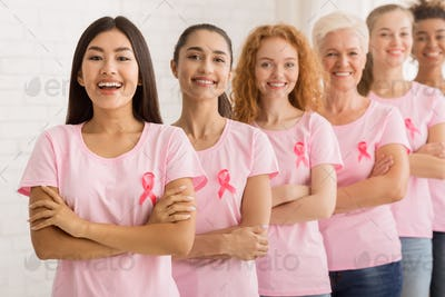 Women In Breast Cancer T-Shirts Standing Next To White Wall