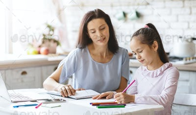Beautiful mother helping her daughter with homework