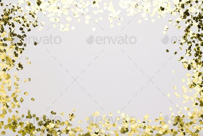 Golden confetti sparkling on white background with copy space