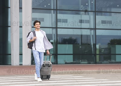 Happy millennial guy going out of airport building