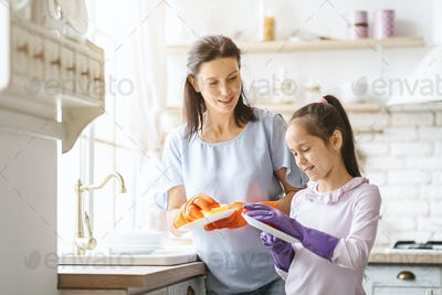 Cute Teenage Girl Helping Mother Washing Dishes At Family Kitchen