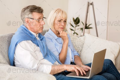 Senior couple reading news on laptop at home
