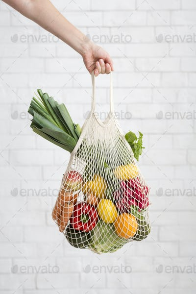 Woman holding mesh shopping bag with colorful vegetables