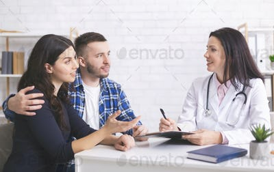 Cheerful doctor talking with millennial family about health care