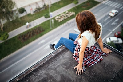 Young brown haired girl sitting on roof