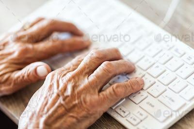 Elderly woman typing on a keyboard