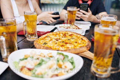 Eating pizza and drinking beer in cafe