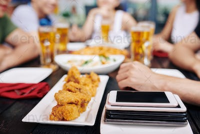 Mobile phones with fast food on the table in cafe