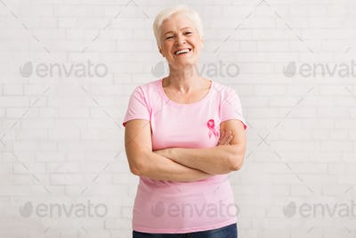 Senior Woman In Pink Breast Cancer T-Shirt Standing Over White Wall