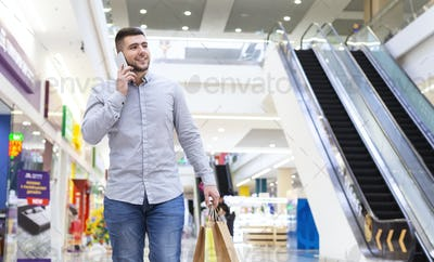 Young man with shopping bags talking by cellphone in mall