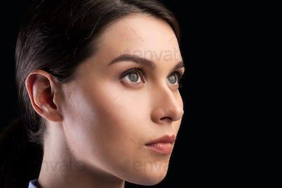 Portrait Of Female Face Staring Aside Over Black Background