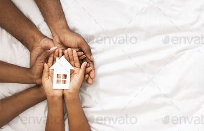 Closeup of paper house in hands of african american family