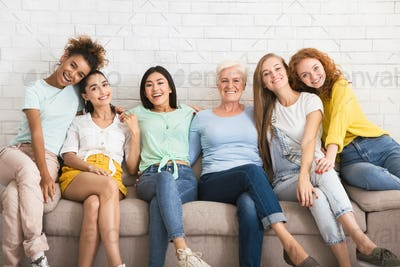 Diverse Women Hugging Sitting On Couch Against White Wall Indoor