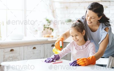 Caring mom teaching daughter how to clean table with detergent