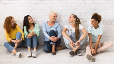 Diverse Ladies Relaxing On Floor Next To White Wall, Panorama