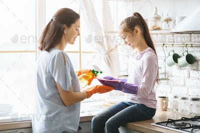 Happy family cleaning house together, little girl helping to mom